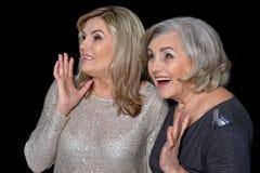 Two beautiful senior women. Posing against black background royalty free stock images