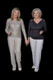 Two beautiful senior women. Posing against black background stock photo