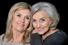 Two beautiful senior women. Posing against black background royalty free stock photo