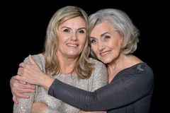 Two beautiful senior women. Posing against black background royalty free stock photography