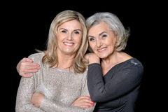 Two beautiful senior women. Posing against black background stock photos