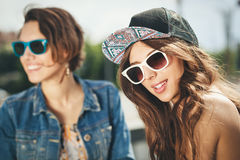Two beautiful and sensuality girls. Two beautiful happy girls in sunglasses looking into the distance on the urban background. Young active people. Outdoors Royalty Free Stock Photography