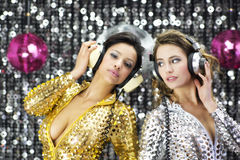 Two beautiful sexy disco women in gold and silver catsuits danci Royalty Free Stock Images