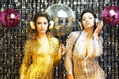 Two beautiful sexy disco women in gold and silver catsuits danci Royalty Free Stock Image