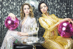 Two beautiful sexy disco women in gold and silver catsuits danci Royalty Free Stock Photos