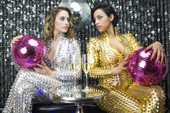 Two beautiful sexy disco women in gold and silver catsuits danci Stock Photography