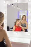 Two beautiful sexy elegant girl in a red and black evening dresses with bright evening make-up evening hairstyle and ticks on his Stock Photos