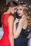 Two beautiful elegant girl in a red and black evening dresses with bright evening make-up evening hairstyle and ticks on his Stock Image