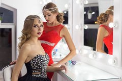 Two beautiful sexy elegant girl in a red and black evening dresses with bright evening make-up evening hairstyle and ticks on his Stock Images