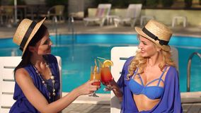 Two sexy girls with cocktails by the pool. Two beautiful sexy girls in bikini and silk dresses sitting on the sun loungers by the pool and clink glasses with a stock video