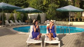 Two girls in bikini drinking cocktails by pool. Two beautiful sexy girls in bikini and silk dresses sitting on the sun loungers by the pool and clink glasses stock video