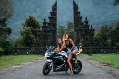Two beautiful sexy girls are sitting on a motorcycle colour black and white. Models dressed in black jerseys and denim. Shorts are posing on a bike. women Stock Photos