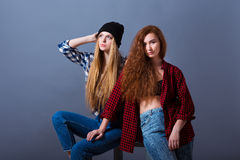 Two beautiful young girls in jeans. Fashion stock images