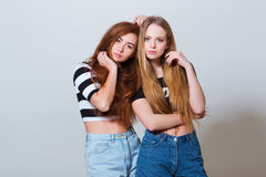 Two beautiful young girls in jeans shorts on royalty free stock photos