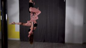 Two beautiful sexy young women in black underwear spinning on a pole