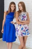 Two beautiful young women friends in beautiful fashion dress in the studio posing for the camera Stock Photo