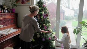 Two sisters decorating Christmas tree with a balls. Two beautiful sisters decorating the Christmas tree in the home. One of the girls sitting on his haunches in stock video footage
