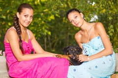 Two beautiful sisters with puppy Royalty Free Stock Images