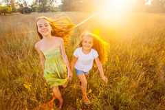 Two beautiful sisters running on the lawn in the nature park outdoor in the summertime. Freedom and carefree. Royalty Free Stock Photos
