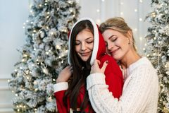 Two beautiful sisters in sweaters hugging near the christmas tree stock photo