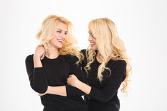 Two beautiful sisters twins looking at each other and smiling Royalty Free Stock Images
