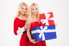 Two beautiful sisters twins in santa claus costumes holding gifts Royalty Free Stock Photography