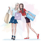 Two beautiful slim girls with shopping bags. Fashion girls. Stylish pretty women. Sketch. Royalty Free Stock Photography