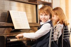 Two beautiful small girls playing piano indoors Royalty Free Stock Photography