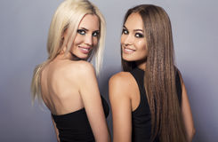 Two beautiful smiling girls with luxurious hair posing in studio Royalty Free Stock Images