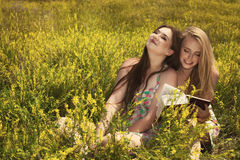 Two beautiful smiling girls reading book against of summer park. Royalty Free Stock Photo