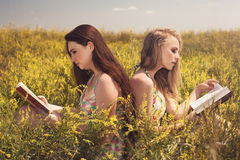 Two beautiful smiling girls reading book against yellow flowers Stock Photos