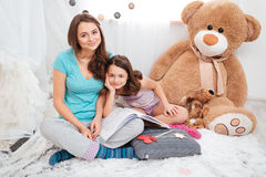 Two beautiful smiling sisters sitting in children room Royalty Free Stock Image