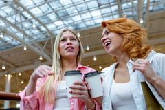 Two beautiful smiling women with disposable coffee cups talking in shopping center. Blur mall as background. Lifestyle. And friendship concepts royalty free stock photography