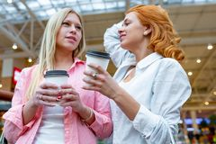 Two beautiful smiling women with disposable coffee cups talking in shopping center. Blur mall as background. Lifestyle. And friendship concepts stock photos