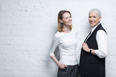 Two beautiful smiling women standing together. Young and senior people Royalty Free Stock Photos