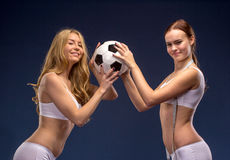 Two beautiful soccer fans hold the ball Royalty Free Stock Photos