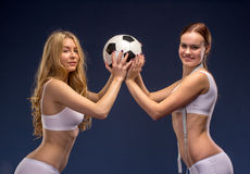 Two beautiful soccer fans hold the ball Royalty Free Stock Image