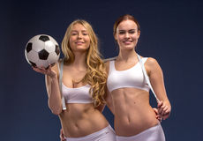 Two beautiful soccer fans hold the ball Royalty Free Stock Images