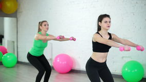 Two beautiful sport woman doing fitness exercise. In fitness centre stock footage