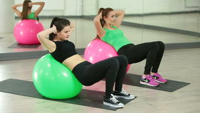 Two beautiful sport woman doing fitness exercise. In fitness centre. Abdominal Exercises stock video footage