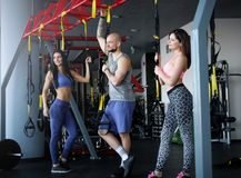 Two beautiful sportive girls with their coach holding functional loops while standing in the gym. Two beautiful sportive girls with their coach holding royalty free stock photos