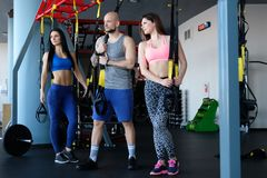 Two beautiful sportive girls with their coach holding functional loops while standing in the gym stock images