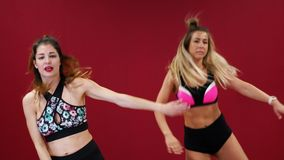 Two beautiful sports girls perform an active fat-burning workout jumping like a kangaroo in special fitness shoes. Cardio workout for endurance stock footage