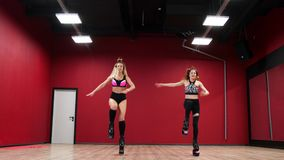 Two beautiful sports girls perform an active fat-burning workout jumping like a kangaroo in special fitness shoes. Cardio workout for endurance stock video footage