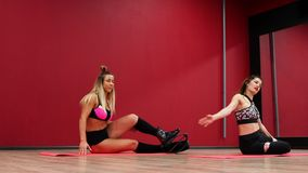 Two beautiful sports girls perform an active fat-burning workout jumping like a kangaroo in special fitness shoes. Cardio workout for endurance. Exercise the stock footage