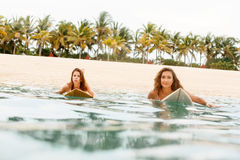 Two beautiful sporty girls surfing in the ocean. Royalty Free Stock Image