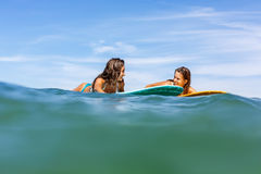 Two beautiful sporty girls surfing in the ocean. Two beautiful sexy surfing girl on surf longboard surfboard board on sunrise or sunset in the ocean. Friends Royalty Free Stock Photography