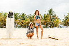 Two beautiful sporty surfer girl at the beach. Royalty Free Stock Images