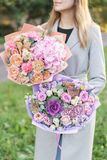 Two beautiful spring bouquet. Young girl holding a flowers arrangements with various of colors. Bright dawn or sunset royalty free stock photos