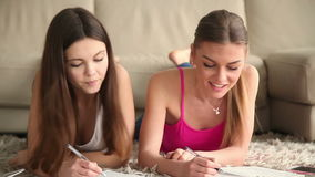Two beautiful student girls studying at home stock footage